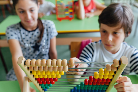 Children working with abacus in the classroom Stock Photo