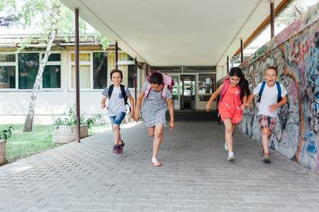 niños saliendo de la escuela: Fin de la escuela. Los niños salen de la escuela feliz. Editorial