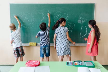 Children writing on blackboard at school