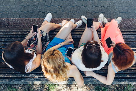 Overhead view of a teenage girls using mobile phones together