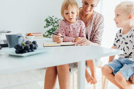 diligente: Feliz madre enseña a sus hijos a escribir