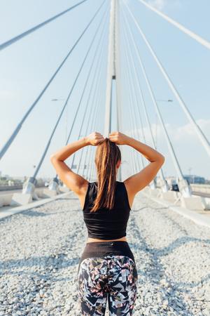 binding: Sporty woman binding hair before workout on the bridge
