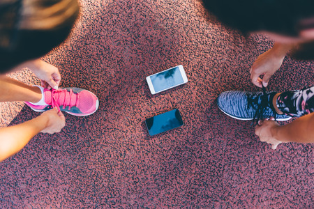 lacing sneakers: Preparation for the  training. Runner women tying running shoes laces getting ready for race on run track with smartphones.