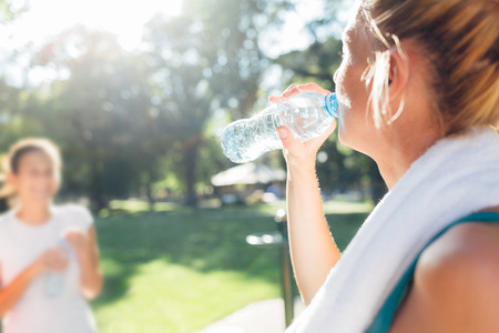Closeup of sportswoman drinking water after workout Stock Photo