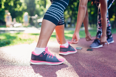 lacing sneakers: Preparation for training in the park Stock Photo
