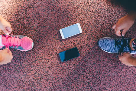 lacing sneakers: Top view of runner women tying running shoes laces getting ready for race on run track with smartphones Stock Photo