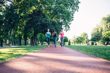 jogging track: Beautiful three young women running on a jogging track in the city park