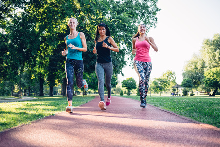 jogging track: Three beautiful  women running on a jogging track in the park Stock Photo