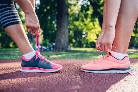 lacing sneakers: Preparation for the race. Closeup of sports woman against each other. Stock Photo