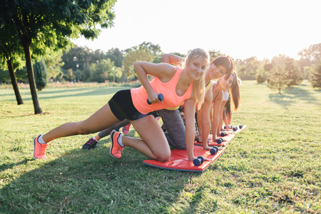 Beautiful sportswomen doing exercise with dumbbells in the park