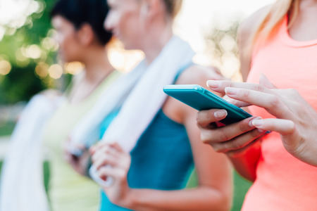 resting heart rate: Sports woman checking fitness result on mobile phone in close up Stock Photo