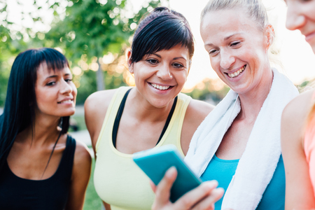 resting heart rate: Happy sports women looking at fitness result on mobile phone Stock Photo
