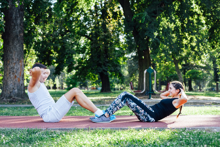 situp: Couples doing crunches together at sport park