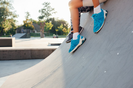 skate park: Womens and mens legs wearing sports shoes, couple sitting at the skate park