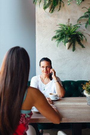 intergenerational: Mother and daughter women in a cafe. Mother have a phone call. Stock Photo