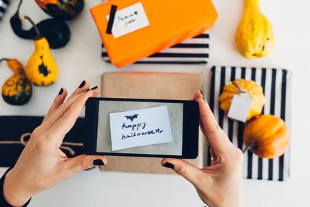 simplicidad: La mujer toma una imagen de la tarjeta de felicitación del feliz Halloween en los presentes envueltos Foto de archivo