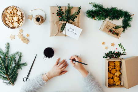 Woman writing Greeting Card for Christmas presents