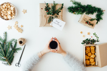 homemade cake: Woman holding tea and packing Christmas presents Stock Photo