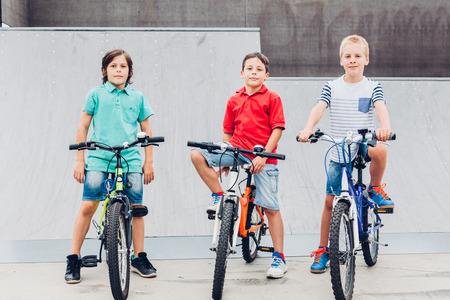 skate park: Boys sitting on their bicycles in a skate park Stock Photo