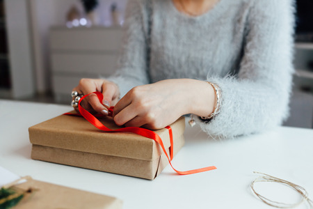 Woman packing Christmas gifts presents with red ribbon Imagens