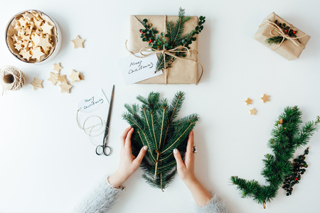 Woman packing Christmas presents with fresh pine twigs