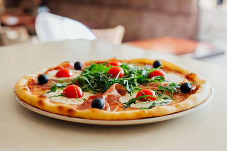Pizza with ham, mozzarella, rocket and chillli tomato on wooden table