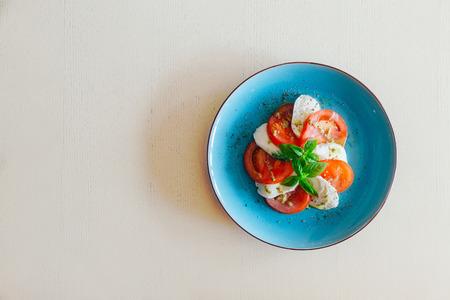 モッツァレラチーズと新鮮なバジルとケッパー コピー スペースが付いている青い皿にトマトのスライス