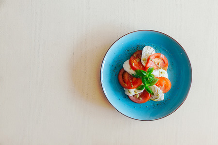 Slices of mozzarella and tomato with fresh basil and capers on blue dish with copy space Standard-Bild