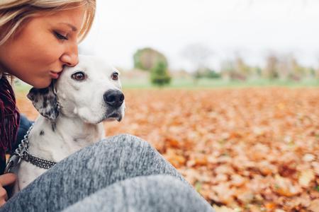 Close-up van gelukkige eigenaar vrouw zoenen hond in de herfst park met lege ruimte