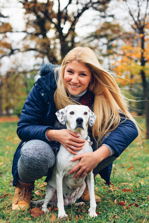 endear: A beautiful woman and his dog posing outside