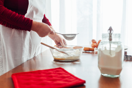 Woman uses the flour to make cakes Stock Photo