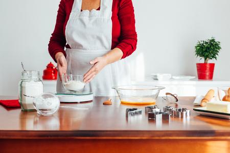 Woman measure flour on kitchen scale Imagens