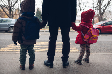 Father with young children waiting for the school bus