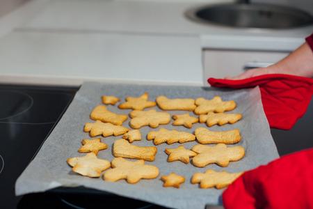 galletas integrales: La mujer está sosteniendo una bandeja para hornear con las cookies de Navidad al horno Foto de archivo