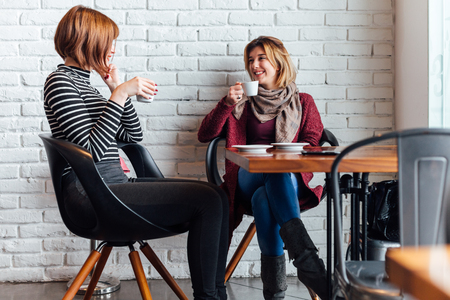 Two happy women drinking coffee at cafe Banco de Imagens