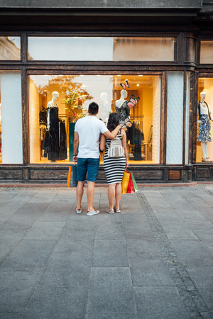 shop window: A beautiful couple is looking at a boutique window shop with copy space Stock Photo