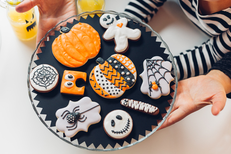Closeup of mom and daughter holding Halloween cookies