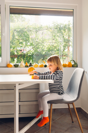 Little girl sitting on a chair in the dining room Stock Photo
