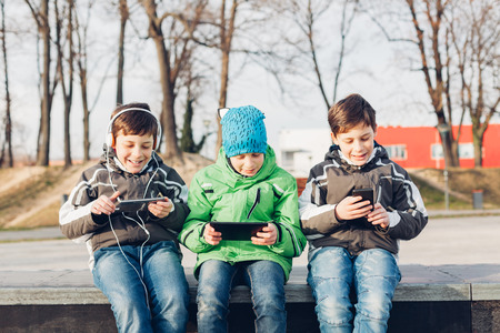 Three boys using mobile phones in the park