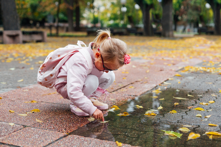 Preschool girl is playing with autumn leaves in a pond