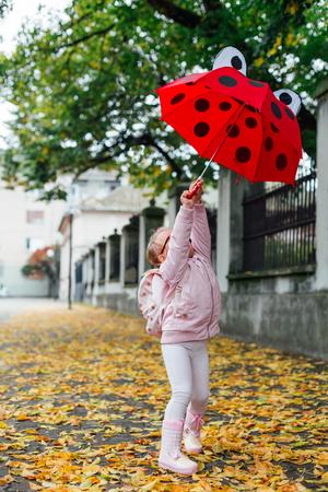 Preschool girl with ladybag umbrella playing on the autumn street
