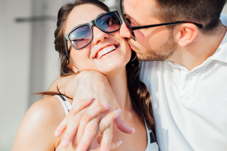 Closeup portrait of happy smiling couple in love. Wearing summer clothes and sunglasses. Stock Photo