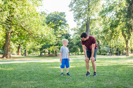 Father and son fitness, stretching in the park. Father and son together.