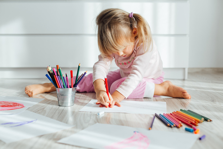 Cute little girl drawing at home