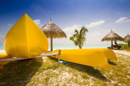 sunshades: yellow canoe at a beach with sunshades and blue sky