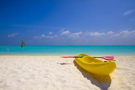 yellow kayak at the beach and windsurfer at the sea