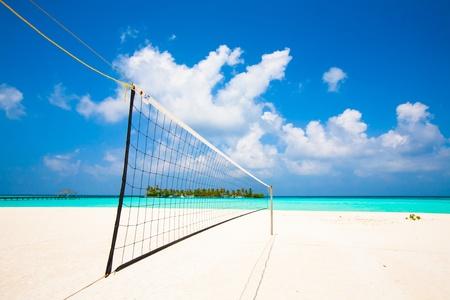 Blick von einem Volleyballnetz am Strand einer tropischen Insel im türkisfarbenen Meer