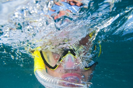 portrait of a man with snorkle and diving goggles under water photo
