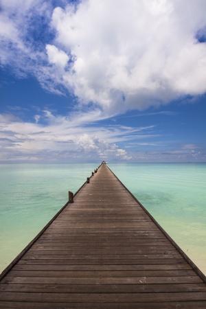 地平線にターコイズ ブルーの海につながる木製の桟橋