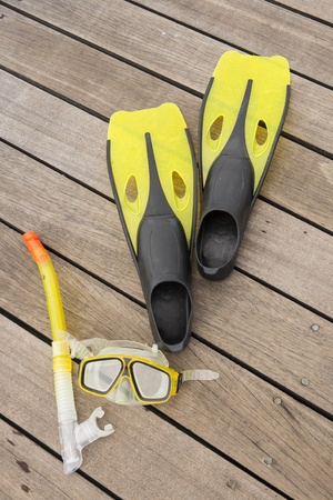 diver eyeglasses, diving goggles, snorkel and fins on the jetty Standard-Bild